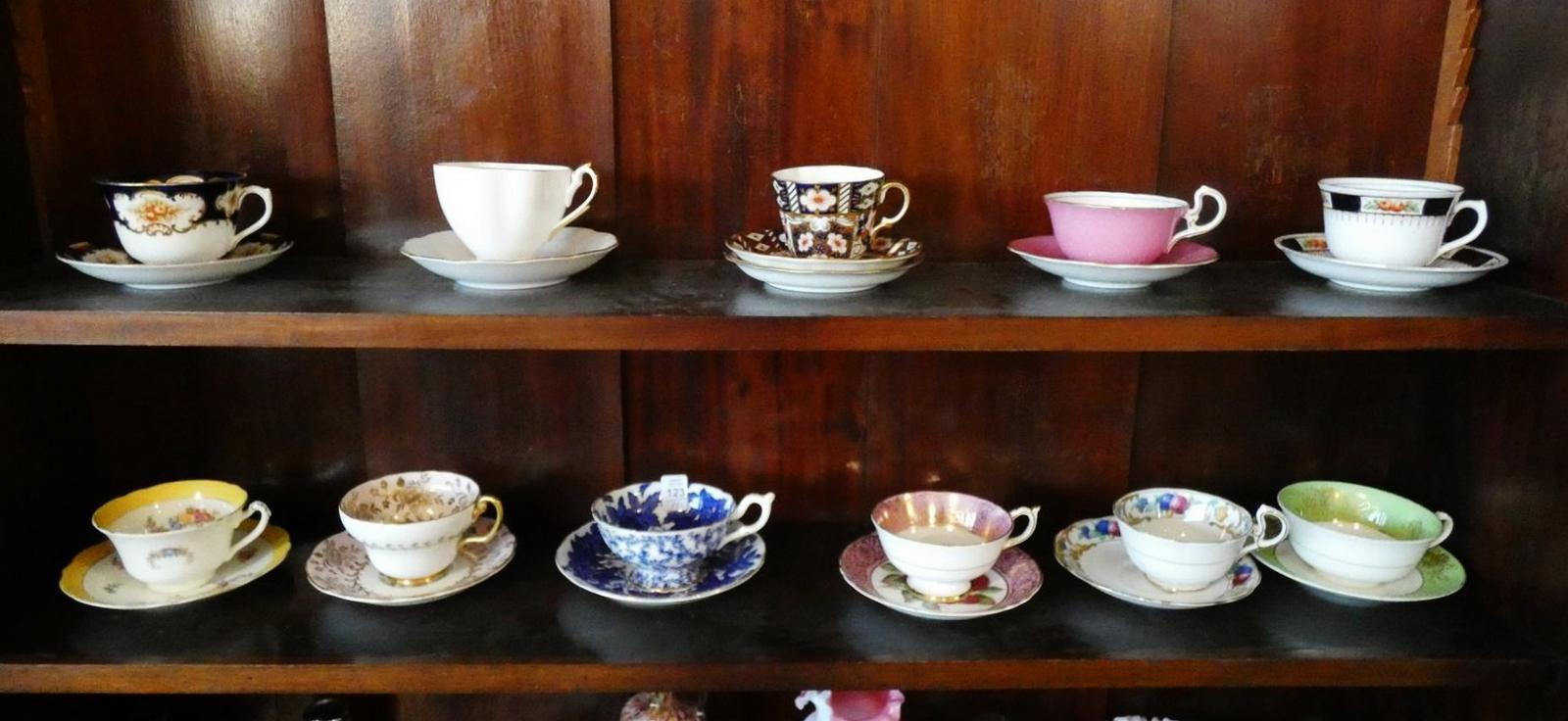 ELEVEN CUPS AND SAUCERS
